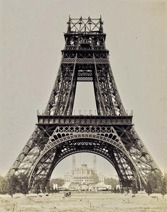 Der Eiffelturm im Bau mit dem Palais du Trocadéro im Hintergrund